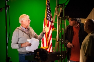 Director John Orland telling actor Martin Bell how to wave cashiers check in the air.